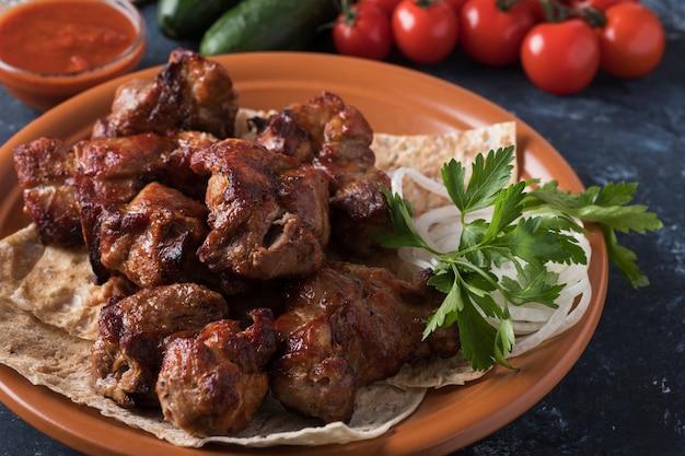 꼬치 케밥에 양파와 고기 조각. 빨간 소스와 함께 접시에 돼지 고기 케밥입니다.