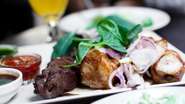 꼬치 케밥에 양파와 고기 조각입니다. 흰 접시에 소스와 함께 제공하십시오.