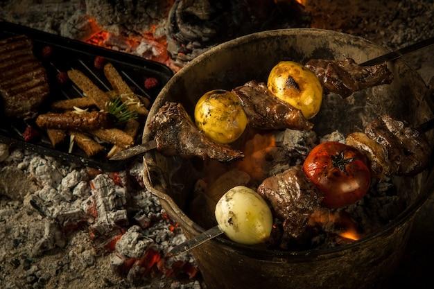 숯불에 구운 토마토와 레몬을 곁들인 고기 조각 요리를 숯불에 굽고 훈제