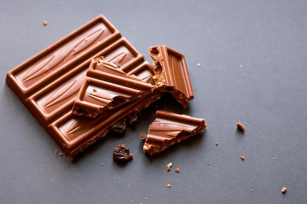 Кусочки молочного шоколада с измельченными фундуками и изюмом с алкоголем на черном backgro