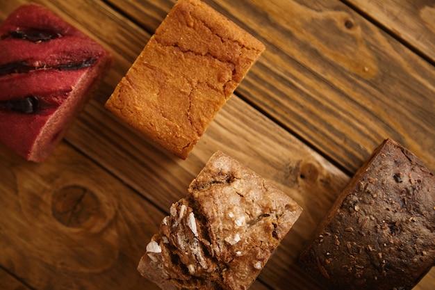 판매용 샘플로 나무 테이블에 다양한 수준으로 제시된 혼합 수제 빵 조각 :