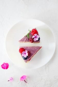 白い皿にムースラズベリーレモンケーキのかけら。砂糖、乳糖、グルテンフリー。垂直方向、上面図、フラットレイ。