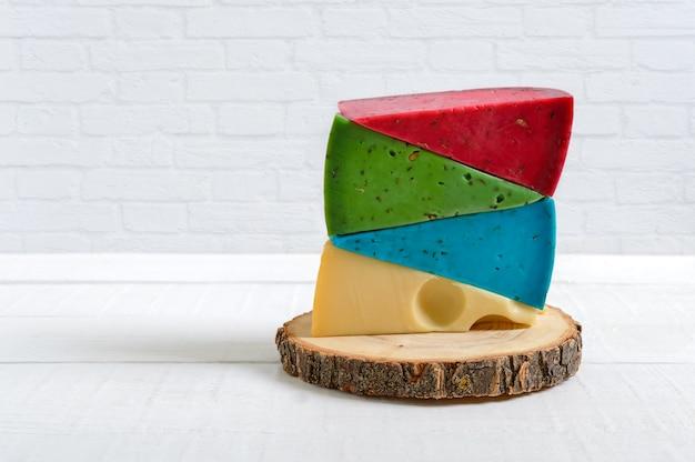 여러 가지 색의 치즈 조각이 가벼운 식탁 위에 쌓여 있습니다. 다양한 종류의 공예 치즈.