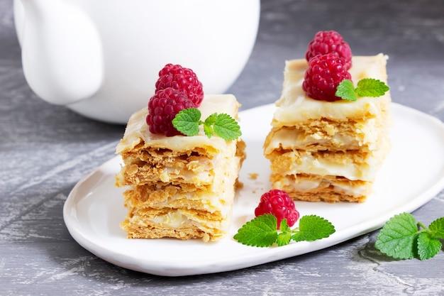 明るい背景にラズベリーとレモンバームの葉で飾られたナポレオンケーキのかけら。