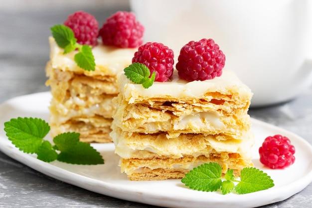Кусочки торта наполеон, украшенные малиной и листьями мелиссы на светлом фоне.