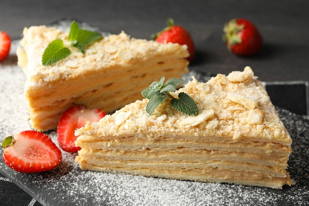 딸기와 설탕 가루와 나폴레옹 케이크의 조각을 닫습니다.