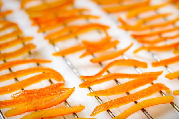 Кусочки апельсиновой корки сушат на гриле.
