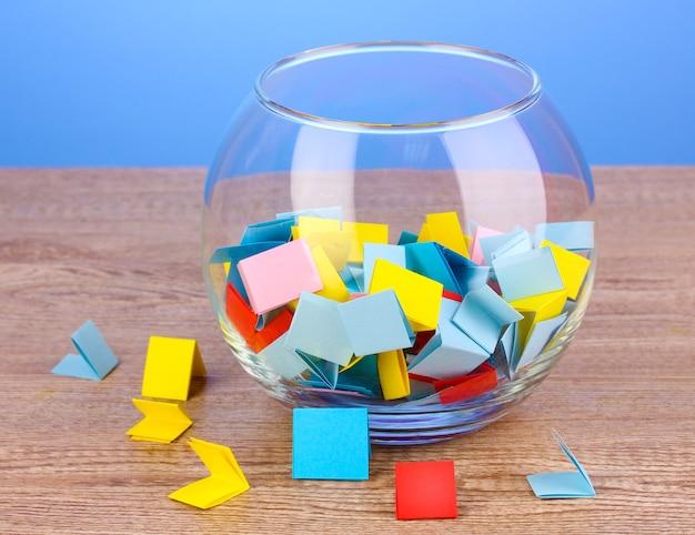 Кусочки бумаги для лотереи в вазе на деревянном столе