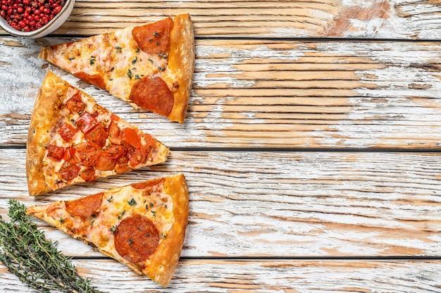 Кусочки пепперони и томатной пиццы. белый деревянный фон. вид сверху. скопируйте пространство.