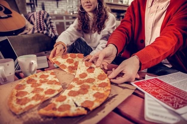 ピザのかけら。一緒に勉強した後、ピザのかけらを取っている空腹の勤勉な学生のクローズアップ