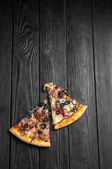 짙은 검은색 나무 판자에 피자 조각, 전통적인 이탈리아 피자