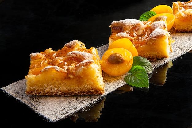 黄色い梅とミントの葉で飾られた粉砂糖入り梅ケーキ