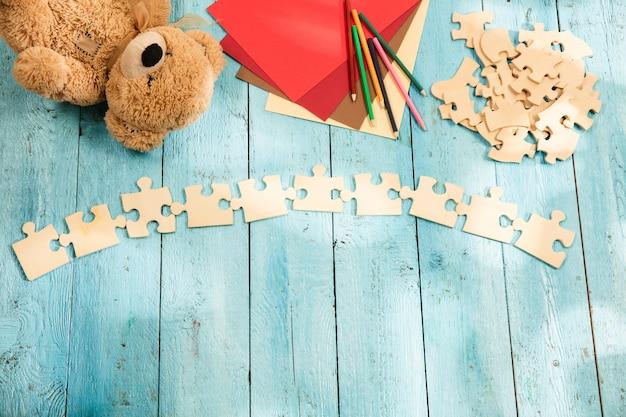 Кусочки пазла, мелки, игрушечный медведь и бумага на деревянном столе. понятие детства и образования.