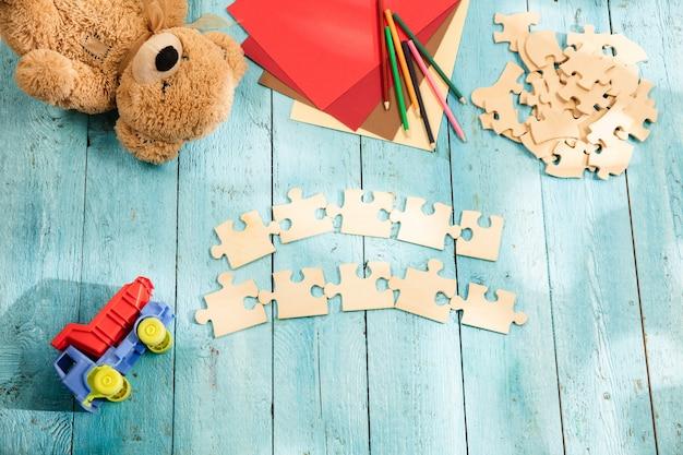 パズルのピース、クレヨン、おもちゃのトラック、テディベア、木製のテーブルの上の紙。子供の頃と教育の概念。