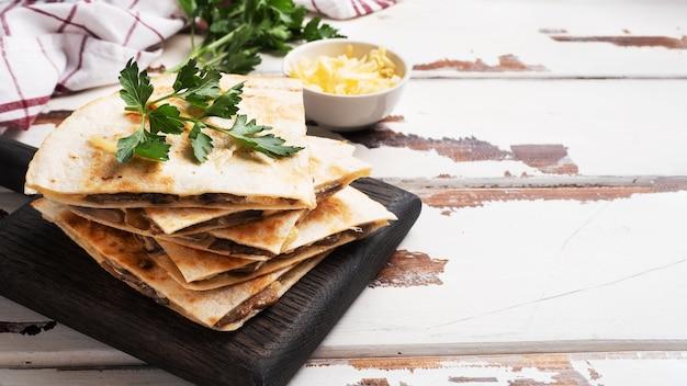 Кусочки кесадильи с грибами, сметаной и сыром