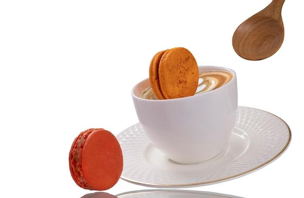 傾いた一杯のコーヒーに落ちるレンジマカロンのかけら