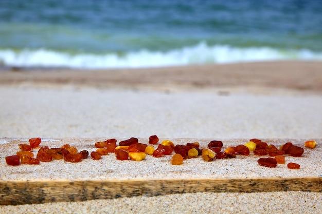 Кусочки необработанного янтаря разбросаны по песчаному пляжу.