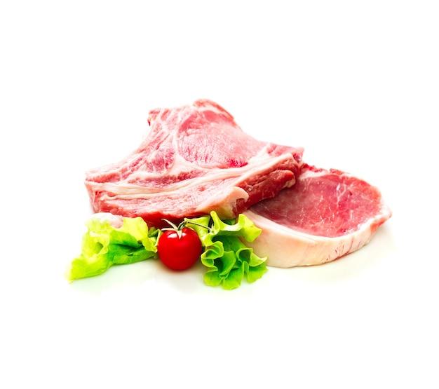 흰색 배경에 분리된 토마토와 샐러드를 곁들인 생 쇠고기 조각