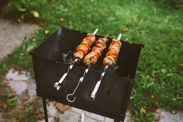 토마토와 양파 링으로 다진 고기 조각은 바베큐에서 요리됩니다.
