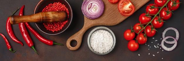 Кусочки сырого стейка из свинины на разделочной доске с помидорами черри, розмарином, чесноком, красным перцем, лавровым листом, луком, солью и ступкой для специй на ржаво-коричневом фоне. вид сверху с пространством для вашего текста.