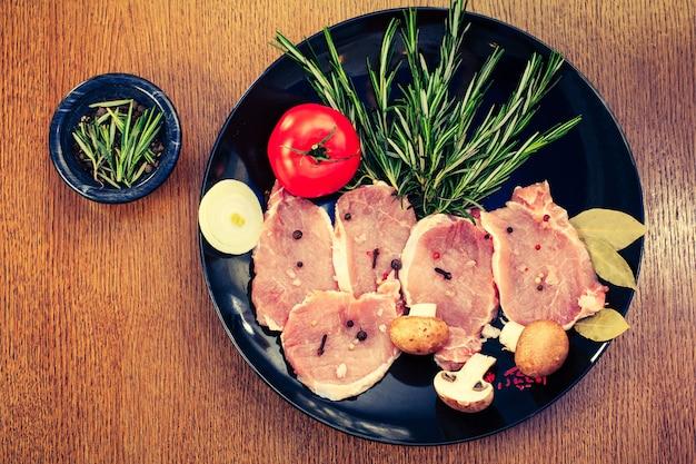 生のポークステーキとスパイスとハーブのローズマリー、マッシュルーム、トマト、タマネギ、塩とコショウ、黒いプレートの月桂樹の葉、上面図