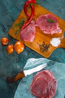 향신료와 허브 로즈마리와 원시 돼지 고기 스테이크 조각