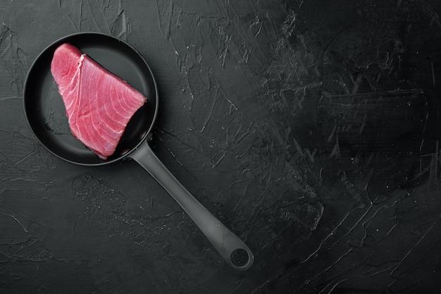 Набор кусочков сырого тунца на сковороде, на черном камне