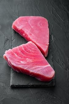 Набор кусочков сырого тунца, на каменной доске, на черном камне