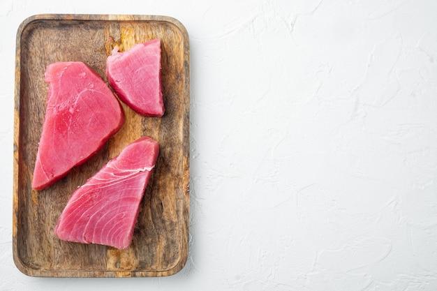 Набор кусочков сырого тунца, на деревянном подносе, на белом камне