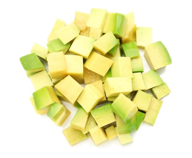 Кусочки спелого авокадо на белой поверхности