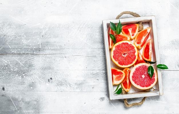 トレイに熟したグレープフルーツのかけら。白い素朴な背景に