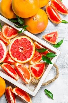 Кусочки спелого грейпфрута на подносе.