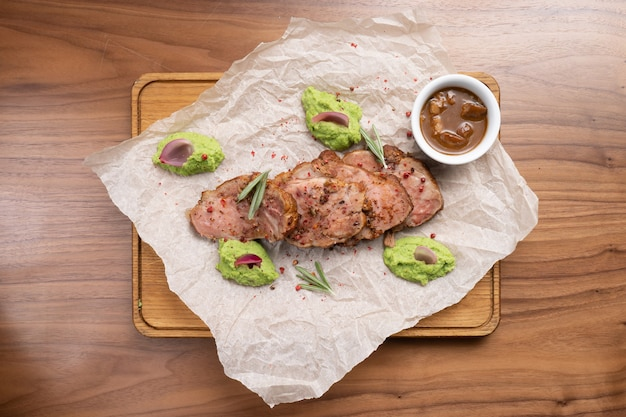 Кусочки жареной свинины со специями, розмарином, гороховым пюре и соусом на деревянном столе