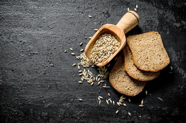 Кусочки ржаного хлеба с зерном. на черной деревенской поверхности