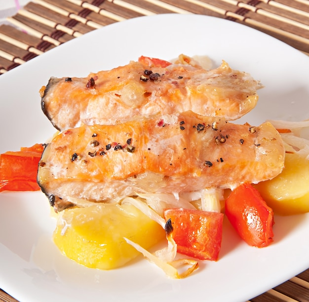 Кусочки лосося с картофелем, помидорами и луком, запеченные в духовке