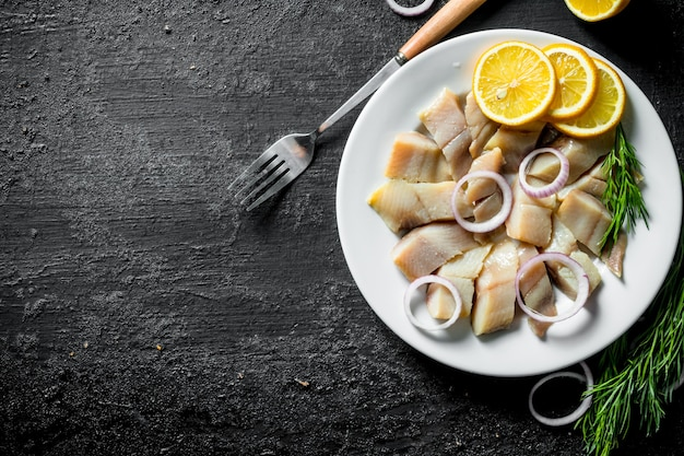 Кусочки соленой сельди на тарелке с нарезанным лимоном и луком. на черном деревенском фоне