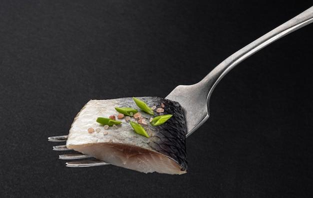 Кусочки соленой сельди на вилке на черном