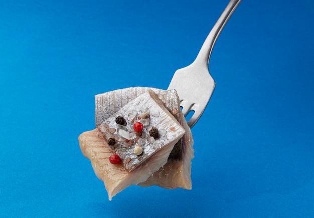 Кусочки малосольной сельди на вилке, кусочки копченого маринованного рыбного филе скумбрии