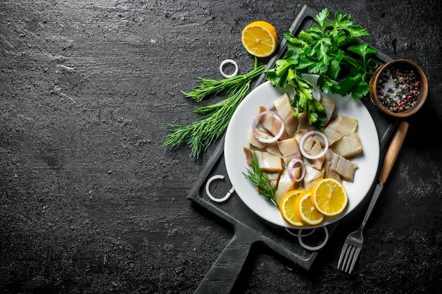 Кусочки малосольной сельди с зеленью, специями и лимоном. на черном деревенском столе