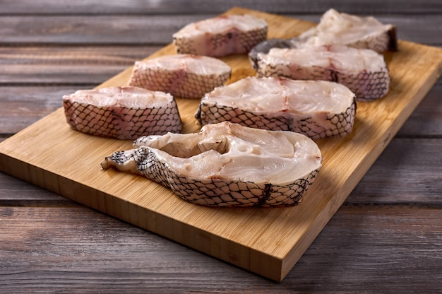 Кусочки нарезанной белой сырой рыбы macrourus на деревянной разделочной доске на деревянном деревенском фоне