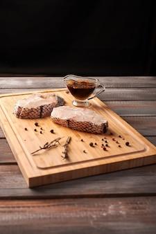 Кусочки нарезанной белой сырой рыбы, оливкового масла, розмарина, перца на деревянной разделочной доске на деревянном деревенском стиле
