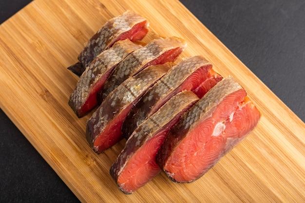 Кусочки копченой рыбы на сервировочной доске. красивая подача к столу. рыба крупным планом