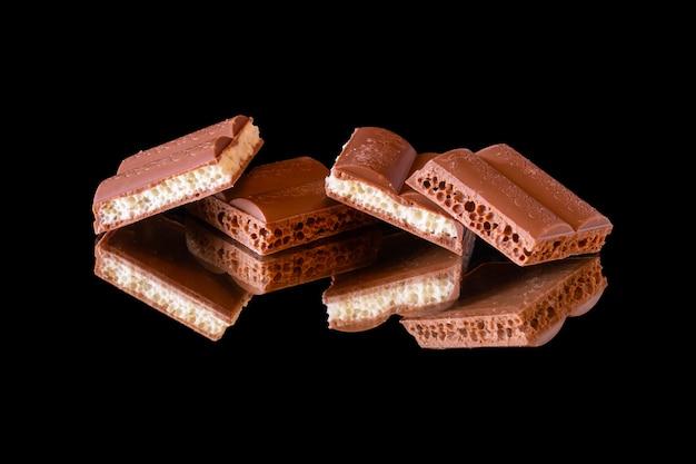 Кусочки квадратного пористого молочного шоколада с темно-белой начинкой отражаются на зеркальной поверхности. изолированные на черном.