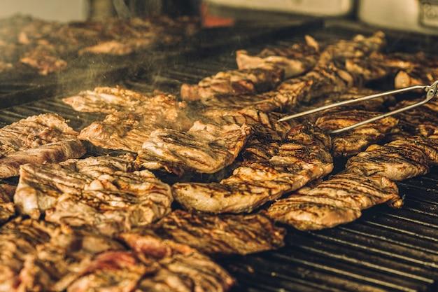 Кусочки стейка медленно готовятся на гриле в ресторане.
