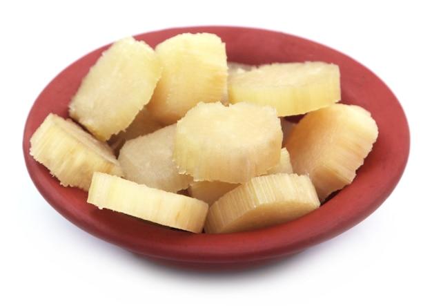 Кусочки сахарного тростника на коричневой миске на белом фоне