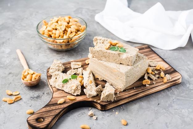 Кусочки подсолнечника и арахисовой халвы и листья мяты на разделочной доске и миску с орехами на столе. калорийный восточный десерт