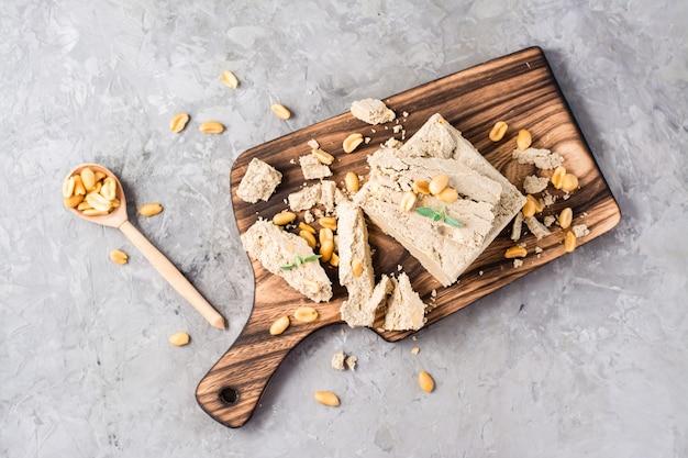 テーブルのまな板にひまわりとピーナッツのハルヴァとミントの葉のかけら。カロリーオリエンタルデザート。上面図