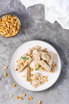 Кусочки подсолнечника и арахисовой халвы и листьев мяты на тарелке и миску с орехами на столе. калорийное восточное лакомство. вид сверху и вертикальный