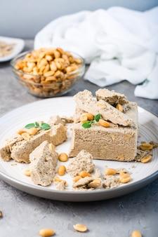 Кусочки подсолнечника и арахисовой халвы и листьев мяты на тарелке и миску с орехами на столе. калорийное восточное лакомство. вертикальный вид. крупный план