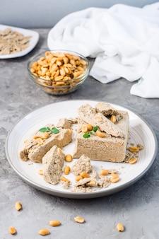 Кусочки подсолнечника и арахисовой халвы и листьев мяты на тарелке и миску с орехами на столе. калорийное восточное лакомство. вертикальный вид